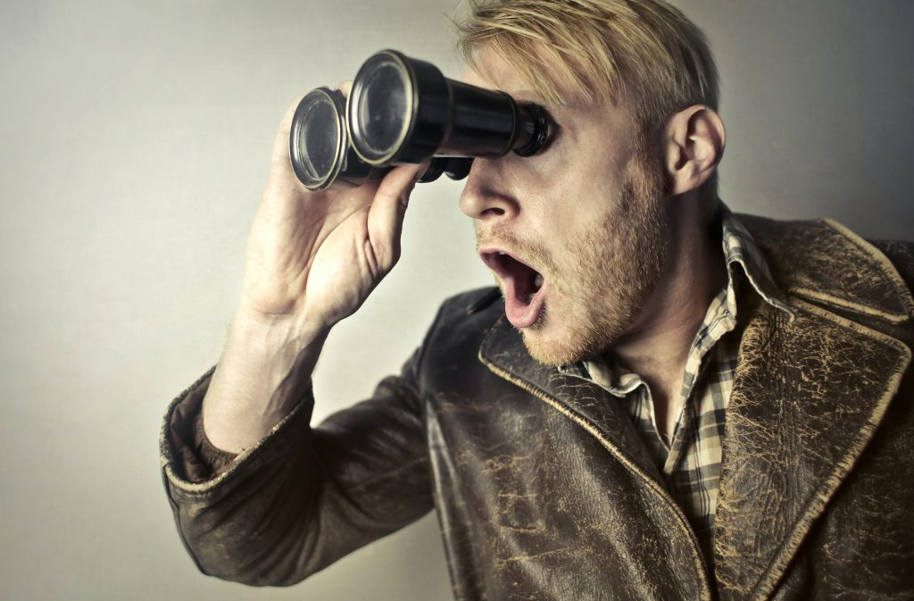 Man with a binocular, a metaphor for searching for B2B leads