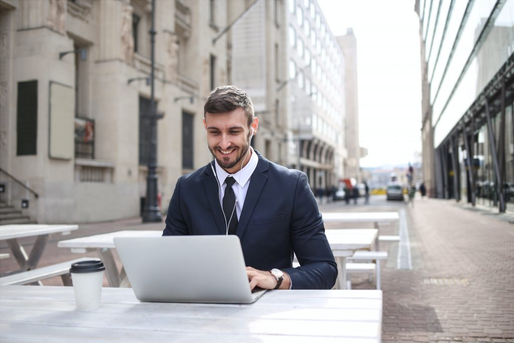 Businessman sitting with a laptop and writing with the help of copywriting tools.